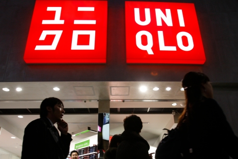 Pedestrians walk past  Fast Retailing's Uniqlo casual clothing store in Tokyo