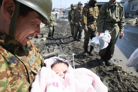 A Japanese officer smiles as he holds a 4-month-old baby girl who was rescued in Ishinomaki, in Miyagi prefecture, on March 14, 2011