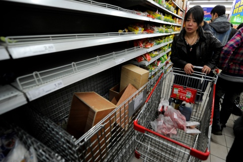 Shoppers look at empty shelves at a supe