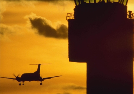 Commercial Airliner Comes In For A Landing Past The Airport Control Tower In De