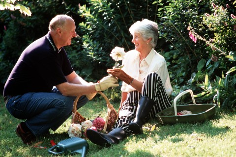 Stock Photography: A portrait of a mature couple aged 50-60 years old, both smiling whilst the man presents the lady with a flower from a basket in a sunlit garden.
