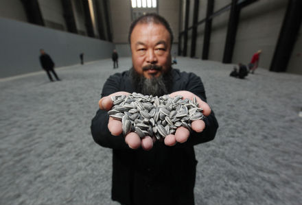 Chinese Artist Ai Weiwei holds some seeds from his Unilever Installation 'Sunflower Seeds' at The Tate Modern on October 11, 2010 in London