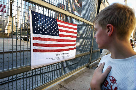 Teenager looks at an American flag which displays the names of those killed September 11, 2001