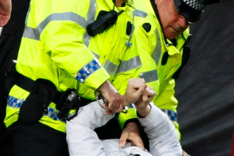 Police hold down a man after he tried to attack Celtic manager Lennon in the dugout area during their Scottish Premier league soccer match against Hearts in Edinburgh, Scotland