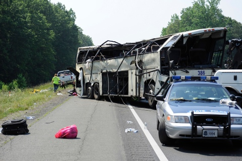 A Virginia State Patrol cruiser sits in front of the aftermath of an early-morning bus crash that killed four people, in the northbound lanes of Interstate 95 in Carmel Church, Virginia