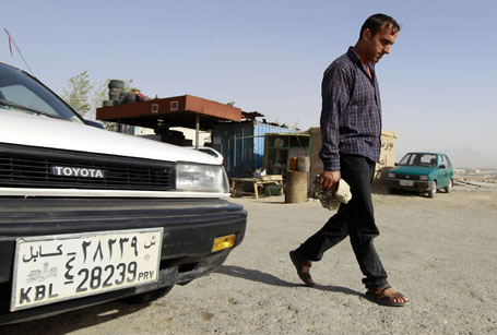 "A man walks past a car with the number ""39"" on its license plate in Kabul"