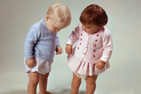 Classic Collection, Page 122, 10420816. Two little children, in a studio shot, little girl dressed in a pink cardigan, little boy dressed in a blue cardigan, both looking at something on the floor. 1967.