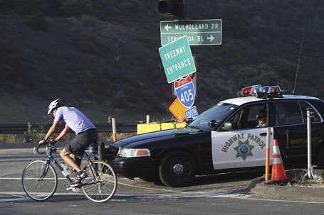 A cyclist passes a California Highway Patrol officer at the 405 onramp from Skirball Center Drive during the demolition of the Mulholland Drive bridge across the 405 freeway in Los Angeles, California.