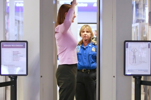 TSA officer scans a woman through with a whole body scan machine, or millimeter wave machine at the Salt Lake International Airport in Salt Lake City