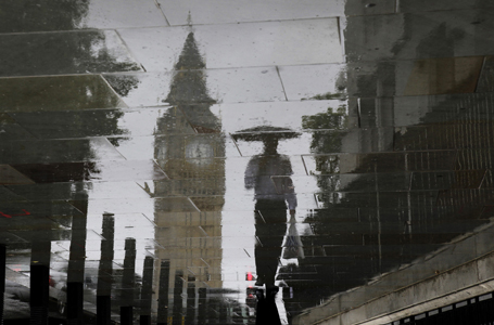 A man is reflected next to Big Ben on a wet pavement during a rainy day in central London