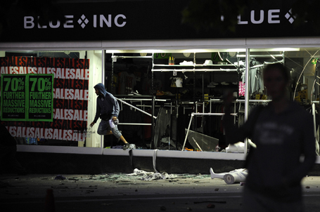 A looter jumps out from a smashed-up department store in Peckham