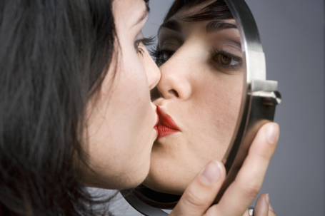 Woman kissing her reflection in mirror