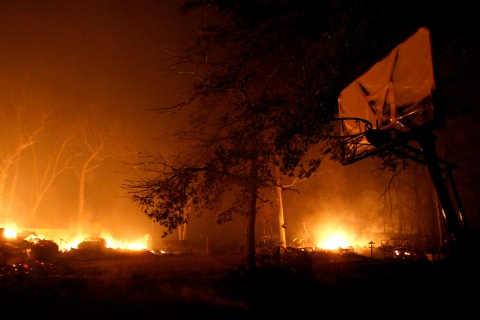 A basketball net can be seen in the foreground as a home burns near Bastrop