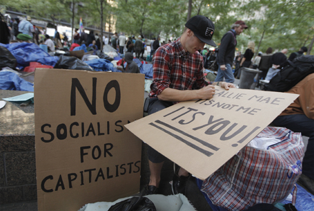 A member of the Occupy Wall Street movement makes signs protesting the financial industry in New York