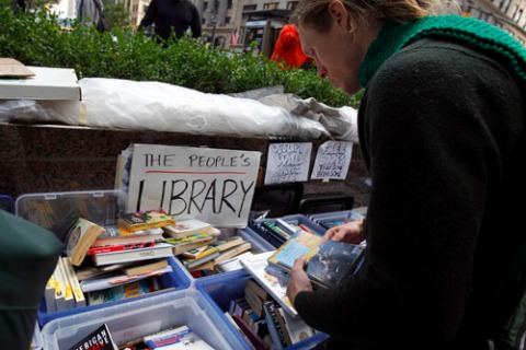 Demonstrator browses books at library of Occupy Wall Street protesters' camp at Zuccotti Park in lower Manhattan in New York
