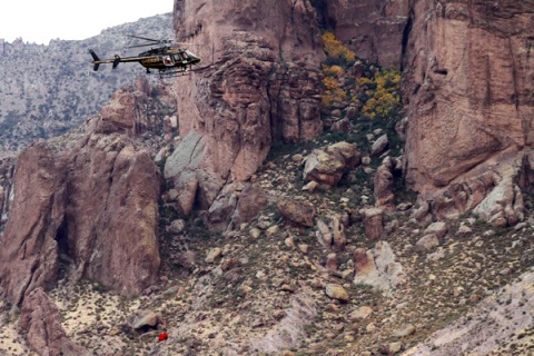A Maricopa Sheriff helicopter recovers a body from the Superstition Mountains where rescue workers searched for victims of a plane crash in Apache Junction
