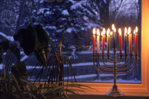 Lit menorah in window during Hanukkah