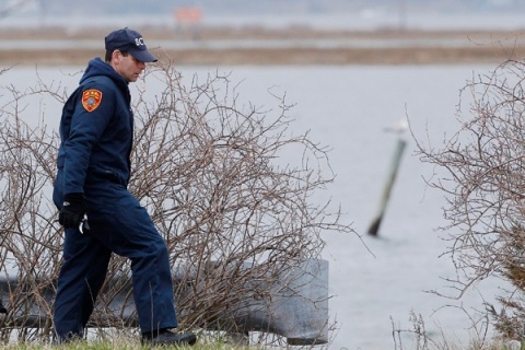 A member of the Suffolk County police search team looks for remains of bodies near the beach area of Oak Beach