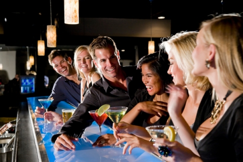 Group of people with drinks flirting at nightclub bar
