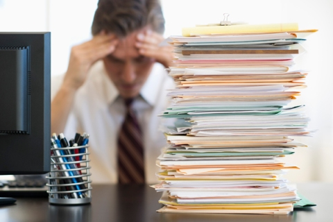 Businessman behind stack of paper, job stress, office