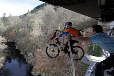 Cyclist Adam Flint, attached to a bungee rope, pedals off the Garry Bridge near Pitlochry, in Scotland