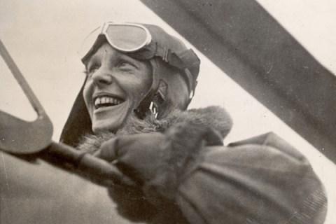 Aviatrix Amelia Earhart in cockpit of plane.