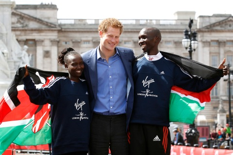 Britain's Prince Harry poses with London Marathon winners Mary Keitany (L) and Wilson Kipsang, both of Kenya, outside Buckingham Palace in London April 22, 2012. REUTERS/Suzanne Plunkett (BRITAIN - Tags: SPORT ATHLETICS ROYALS TPX IMAGES OF THE DAY ENTERTAINMENT)