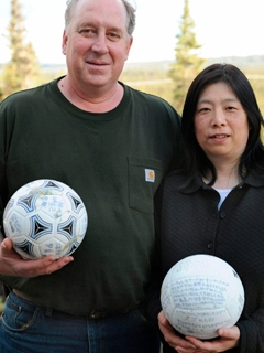David Baxter and his Japanese wife Yumi pose with a soccer ball which they found at a remote site in the Gulf of Alaska
