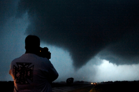 Storm chaser photographer Mack shoots a tornado as it makes its way over the 135 freeway near Moundridge