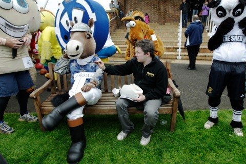 A man offers Ascot Racecourse mascot, Scotty, some food before the Mascot Grand National 2012 at Kempton Park race course in London