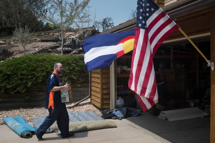 Jeremiah Wetherton helps a friend carry his belongings back into a house in Colorado Springs
