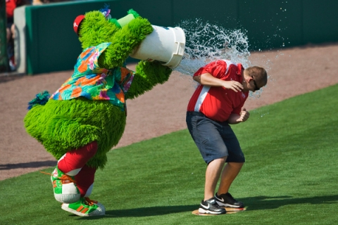 The Phillie Phanatic tosses a bucket of water over a member of the grounds crew during a MLB spring training game