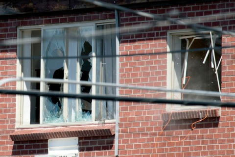 Debris flies out a window after law enforcement officers detonated an explosive device inside the apartment of shooting suspect James Holmes