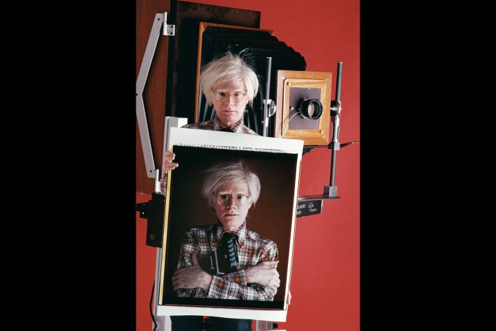 Andy Warhol with Polaroid of himself in 1980 by Bill Ray