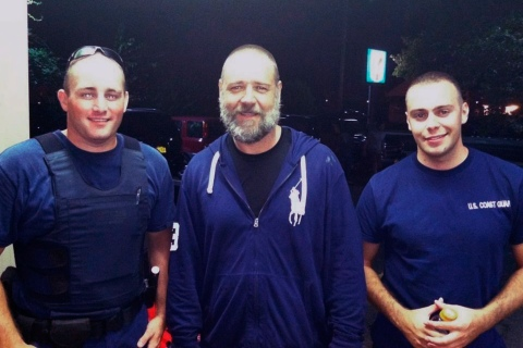 Handout photo of Actor Crowe standing with with U.S. Coast Guard petty officers Swieciki and Watson