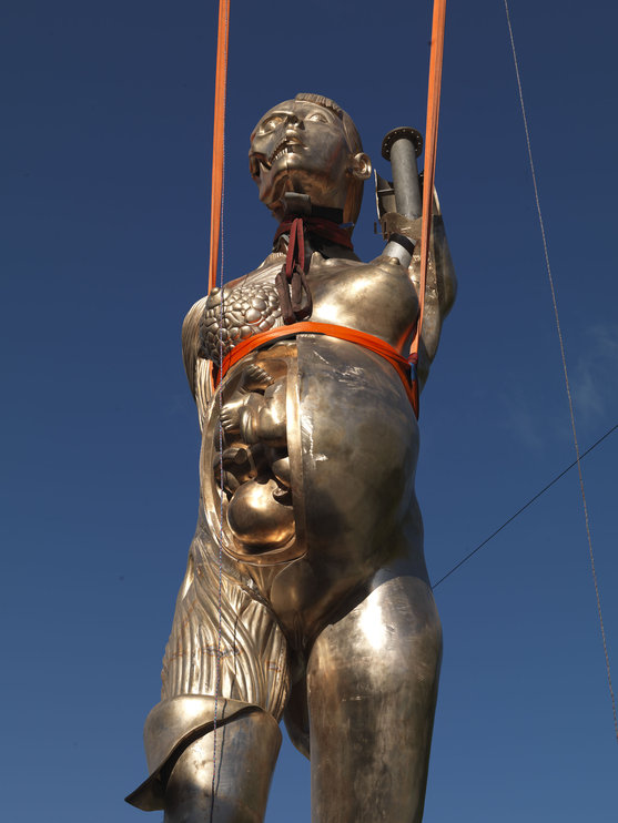 """Damien Hirst's sculpture """"Verity"""" being installed in Ilfracombe, UK."""
