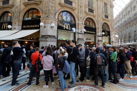 People queue for free meals outside a McDonald's fast food restaurant in downtown Milan