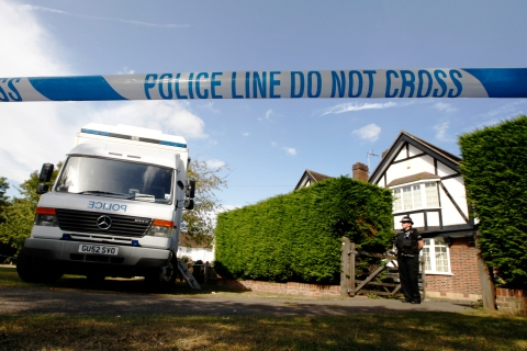 A police officer stands by a cordon close to the house of Saad al-Hilli and his family in Claygate near London