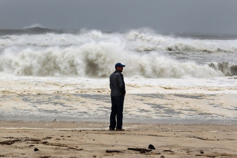 A man stands on the beach to watch the storm surf, kicked up ahead of Hurricane Sandy, in Southampton
