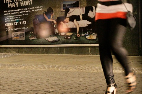 A girl walks past a poster warning of alcohol abuse