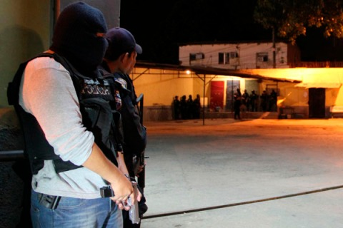 Policemen stand guard while conducting an operation during a prison riot at the prison of San Pedro Sula