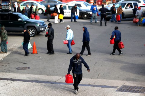 image: Jameel Brown walks away from a pump after filling up a container at a gas station in Newark, N.J., Nov. 2, 2012.