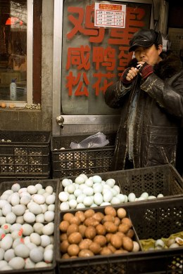 Image: A man smokes a cigarette at an egg stall in Beijing, China, on Dec. 10, 2008.