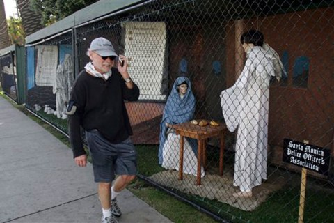 Image: A man walks past two of the traditional Nativity scenes along Ocean Avenue at Palisades Park in Santa Monica, Calif., Dec. 13, 2011.