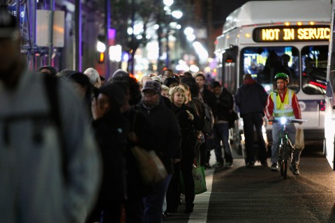 People line up on along a street in Manhattan to take buses back to the Brooklyn borough in the aftermath of Hurricane Sandy in New York
