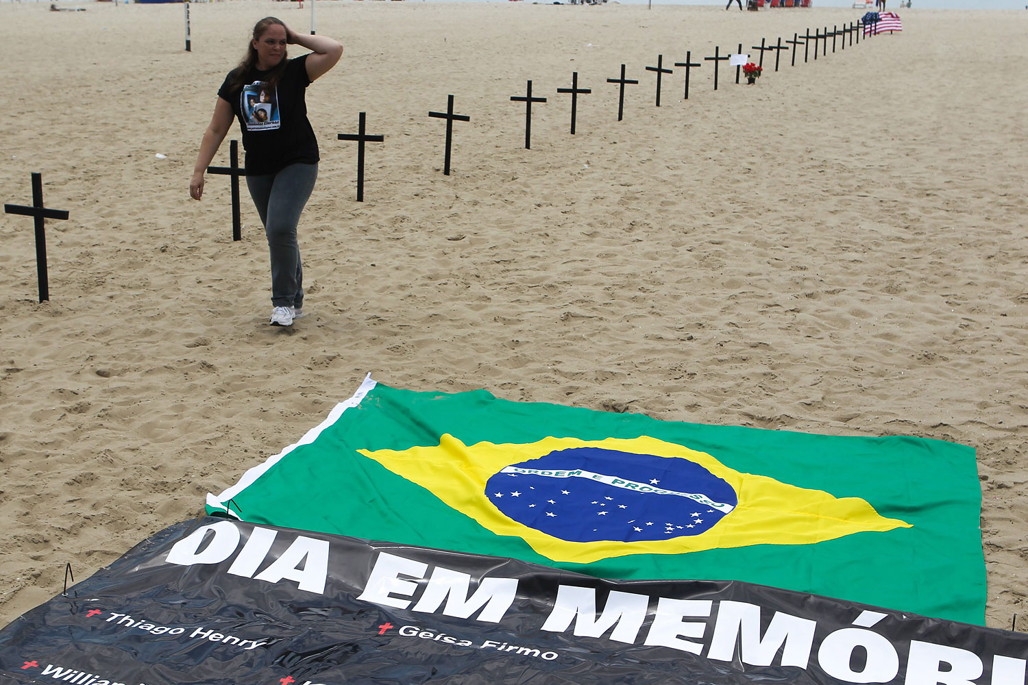 image: A woman walks next to crosses, and a banner reading 'Day of Remembrance' on Copacabana beach, Rio de Janeiro. Brazil, Dec. 15 2012.