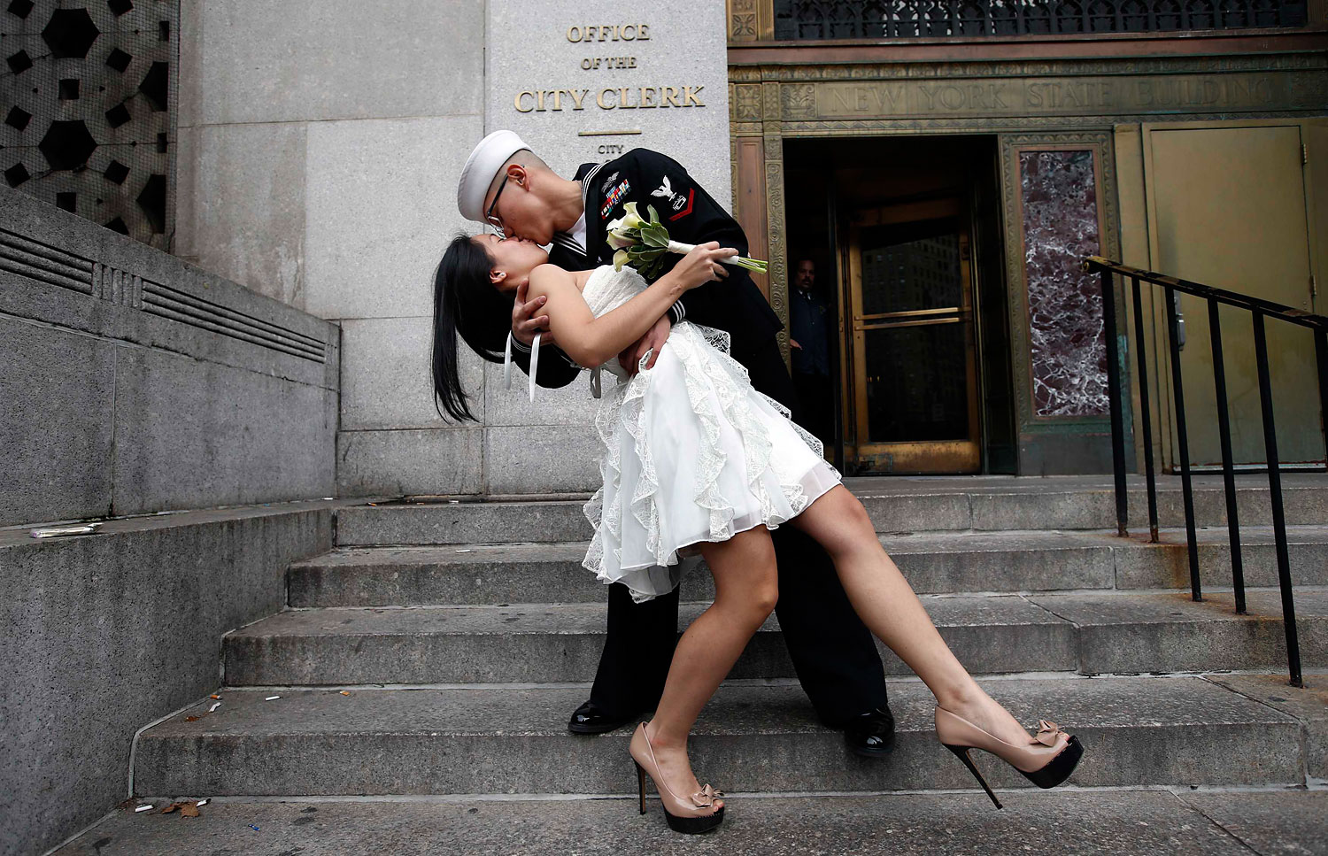 image: U.S. Navy Petty Officer John Chen, 23, of Lakehurst, N.J., kisses his wife Victoria Chan, 25, from Manhattan, after being married in New York City.