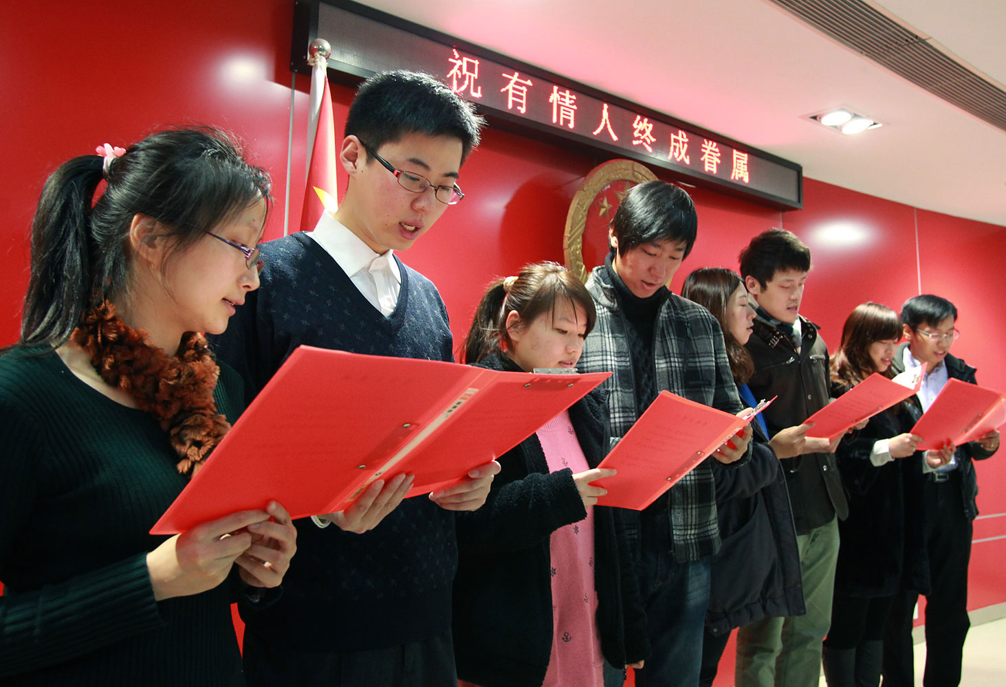 image: Couples read marriage vows in Shanghai.