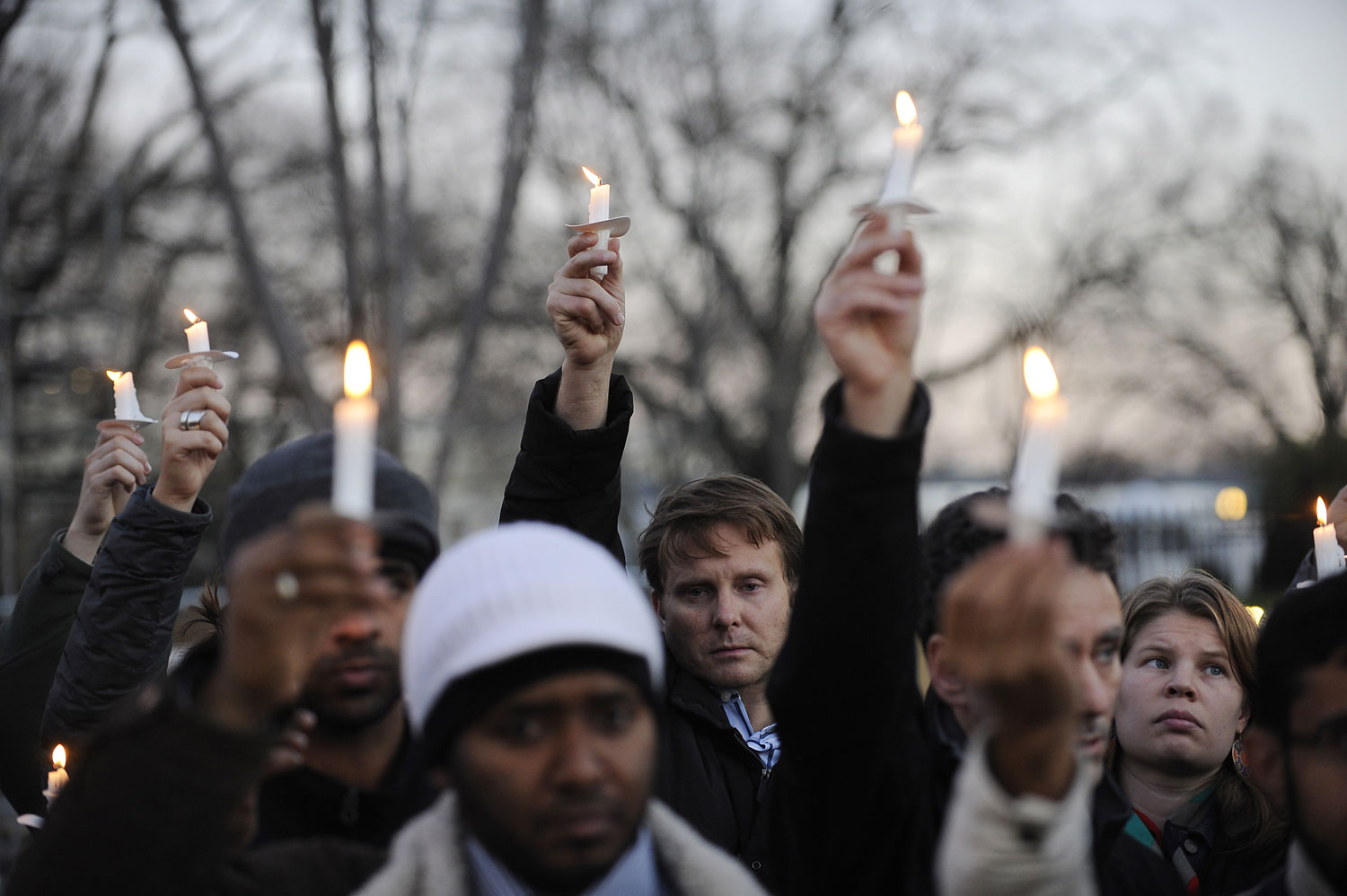 image: Supporters of gun control legislation hold candles and placards during a rally in front of the White House
