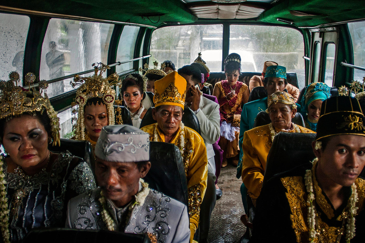 image: Brides and grooms ride a bus in a parade during a mass wedding ceremony in Yogyakarta, Indonesia.